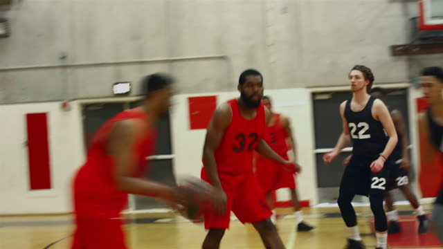 basketball players passing the ball during a game and making a basket - basketball stock videos and b-roll footage