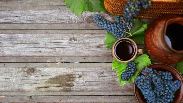 vidéos et rushes de paniers et bol avec raisins à côté de jar et tasse avec le stand de vin sur le bois rustique. fond de fabrication de vin. vue supérieure - pots de bureau