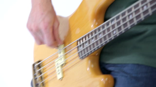 Bass guitar player fingers on the strings close-up isolated on white Bass guitar player fingers on the strings close-up in studio on white background musical theater stock videos & royalty-free footage