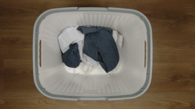 TOP VIEW: Batch of dirty clothes fall to a white laundry basket, Slow Motion video