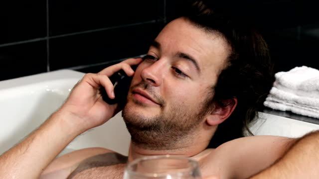stockvideo's en b-roll-footage met bathing man on phone - hd - cell phone toilet