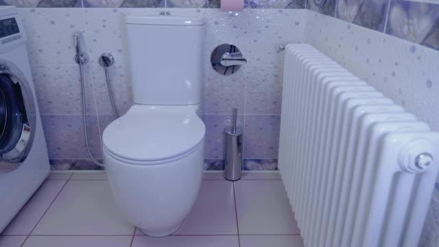 badezimmer interieur: heizkörper, wc, waschmaschine, keramische fliesen mit wandbild - waschmaschine wand stock-videos und b-roll-filmmaterial
