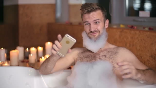 Bathroom Selfie Handsome man taking a selfie in the bathtub with soap foam on his beard bathroom stock videos & royalty-free footage