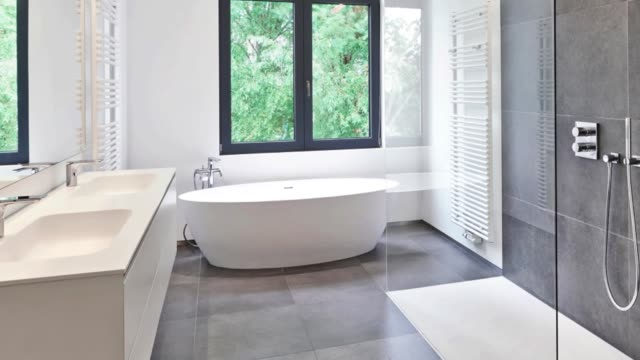 Bathtub in corian, Faucet and shower in tiled bathroom Bathtub in corian, Faucet and shower in tiled bathroom with windows towards garden renovation stock videos & royalty-free footage