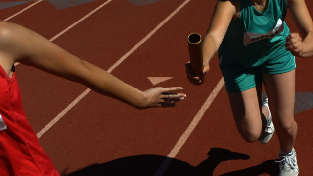 Baton pass in a track relay, slow motion video