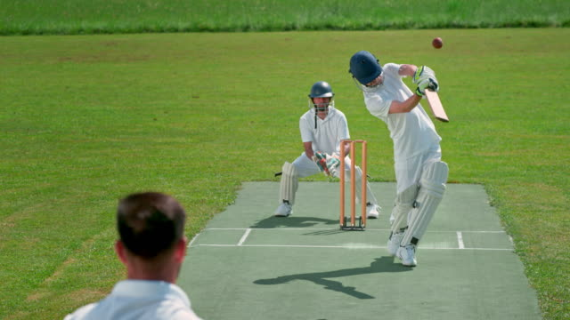 SLO MO LD Batsman striking the ball thrown by the bowler on the sunny field video