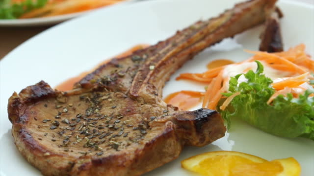 battered fish steak and grilled pork chop steak with bone. colourful salad and vegetable video