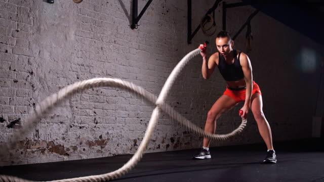 stockvideo's en b-roll-footage met strijd touwen meisje op de sportschool training oefening uitgerust lichaam. slow motion - touw