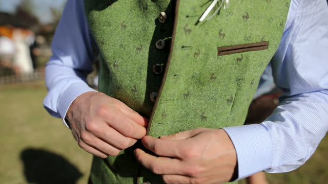 bavarian men buttoning traditional clothes outdoor - costume tradizionale video stock e b–roll