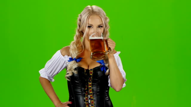 Bavarian woman drinking a beer glass showing thumbs up and winking. Green screen video