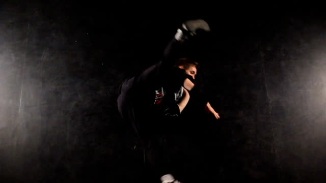 B-boy dancing breakdance in a photo studio on a black background video