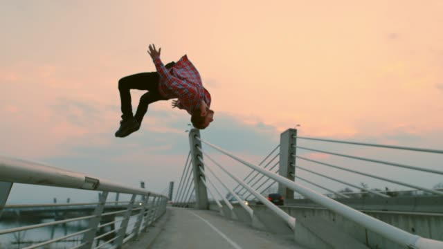 SLO MO B-boy performing a backflip on the bridge
