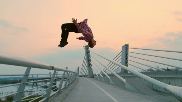 slo mo b-boy performing a somersault from a fence - hip hop video stock e b–roll