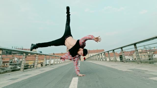 slo mo b-boy utför vissa akrobatiska spinning flyttar - street dance bildbanksvideor och videomaterial från bakom kulisserna
