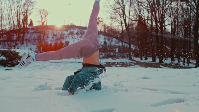 slo mo b-boy spinning on his head in the snow - трюк стоковые видео и кадры b-roll