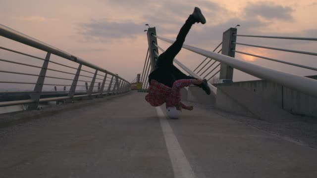 SLO MO B-boy spinning on his head on the bridge