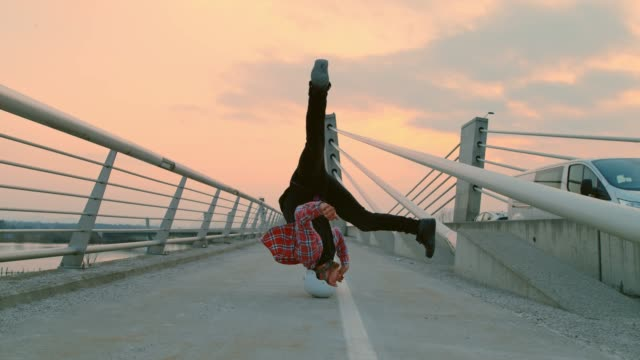 slo mo b-boy spinning on his head on the bridge - hip hop video stock e b–roll