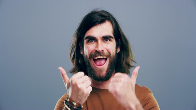 Be awesome today 4k video footage of a man giving thumbs up against a grey background long hair stock videos & royalty-free footage