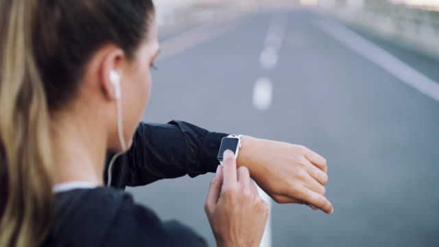 Be better every single day 4k video footage of a young woman checking the time during a workout in the city wristwatch stock videos & royalty-free footage