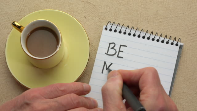 Be mindful - man hand writing a note with a black marker Be mindful - man hand writing a note with a black marker in a spiral notebook, overhead view mindfulness stock videos & royalty-free footage