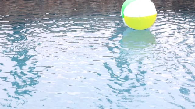 Beach ball floating in refreshing swimming pool water. video