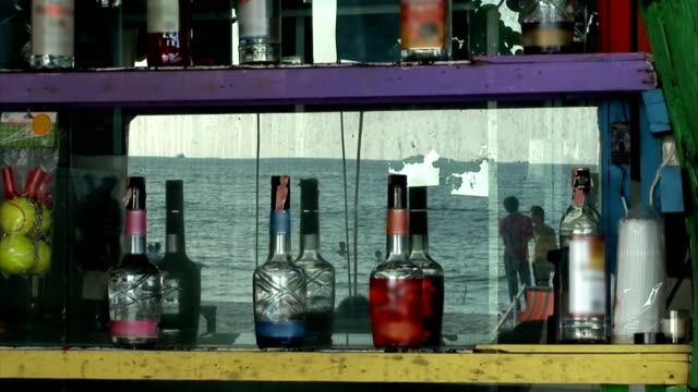 Beach Bar Mirror A shot standing at the bar and looking into the reflection of the dirty mirror. The mirror is behind the bar and has a shelf holding various bottles of liqueur. In the reflection you can see the daily activities of the tourists enjoying the tropical beach. curaçao stock videos & royalty-free footage