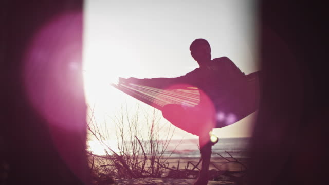 vídeos de stock e filmes b-roll de beach camping. hammock between two pines. lens flares - man admires forest