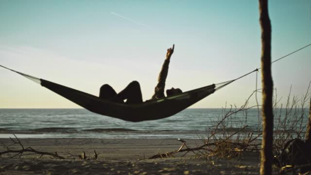 beach camping. hammock between two pines - amaca video stock e b–roll