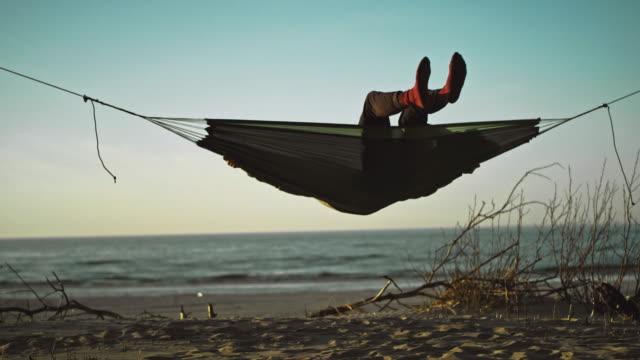 vídeos de stock e filmes b-roll de beach camping. hammock between two pines - man admires forest