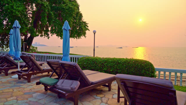 beach chair or pool bed with umbrella around swimming pool at sunset time - vídeo