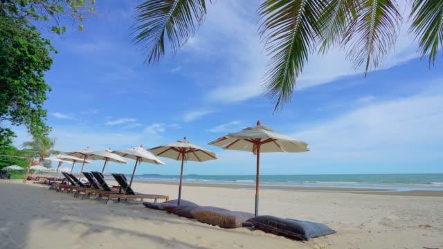 strandkörbe und sonnenschirm über weißem sandstrand. sommer naturblick, themeninsel - sonnenschirm stock-videos und b-roll-filmmaterial