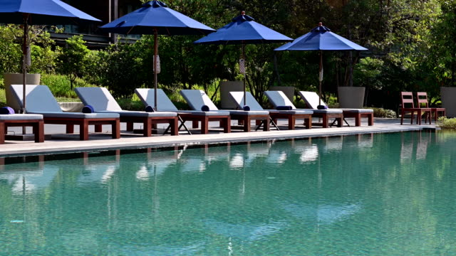 4K Beach chairs near swimming pool in tropical resort
