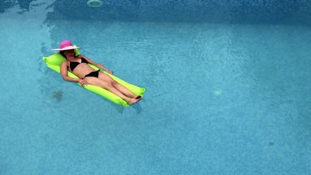 Beach girl having fun relaxing floating in pool water in ocean holiday resort on green pool float toy air mattress. video