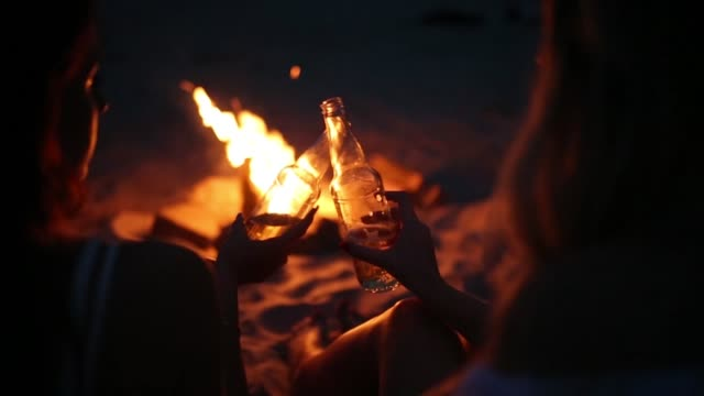 Beach party at sunset with bonfire. Friends sitting around the bonfire, drinking beer and singing to the guitar. Young men and women hold glass bottles with beverage singalong and cheering - video