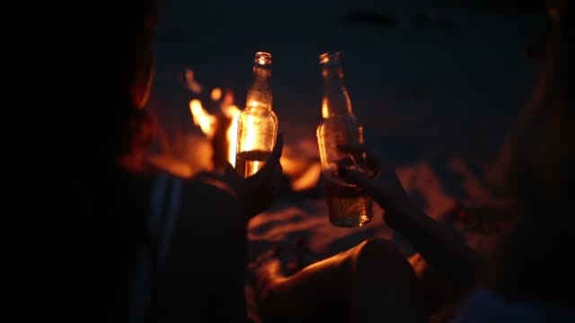 beach party at sunset with bonfire. friends sitting around the bonfire, drinking beer and singing to the guitar. young men and women hold glass bottles with beverage singalong and cheering - birra video stock e b–roll