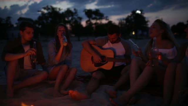 şenlik ateşi ile gün batımında kumsal partisi. şenlik ateşi oturan, bira içip şarkı gitar için arkadaşlar. genç erkek ve kadınların içecek singalong ve tezahürat ile cam biberon - şenlik ateşi stok videoları ve detay görüntü çekimi
