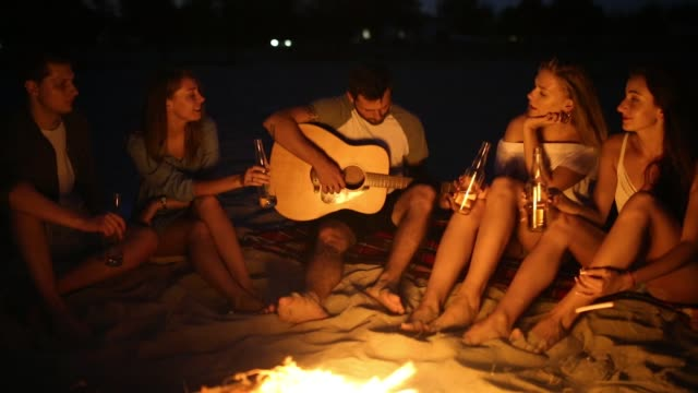 beach party at sunset with bonfire. friends sitting around the bonfire, drinking beer and singing to the guitar. young men and women hold glass bottles with beverage singalong and cheering - falò spiaggia video stock e b–roll