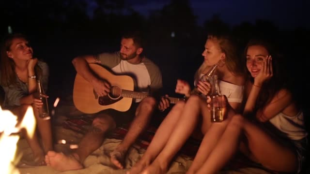 Beach party at sunset with bonfire. Friends sitting around the bonfire, drinking beer and singing to the guitar. Men and women hold glass bottles with beverage singalong, bearded guy playing guitar - video