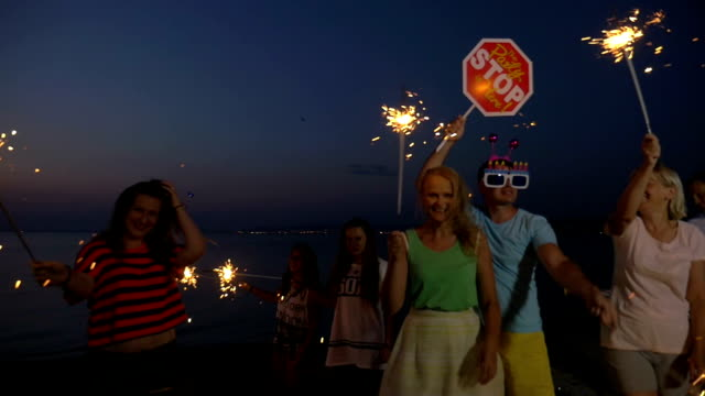 Beach party to celebrate Christmas or New Year Slow motion clip of people having Christmas or New Year celebration at the seaside. Happy family and friends waving with Bengal lights, confetti crackers and party sign petard stock videos & royalty-free footage