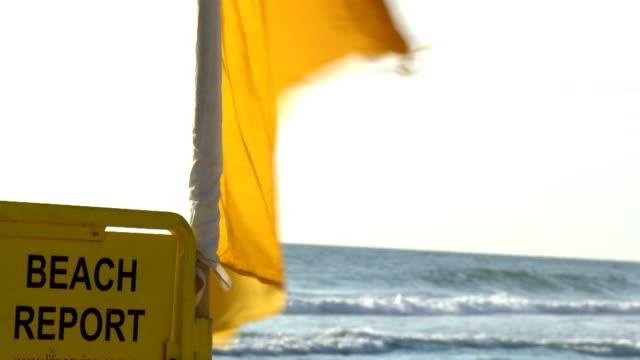 vídeos de stock, filmes e b-roll de praia relatório & amarelo sinal perigoso bandeira de surfe - campeonato esportivo