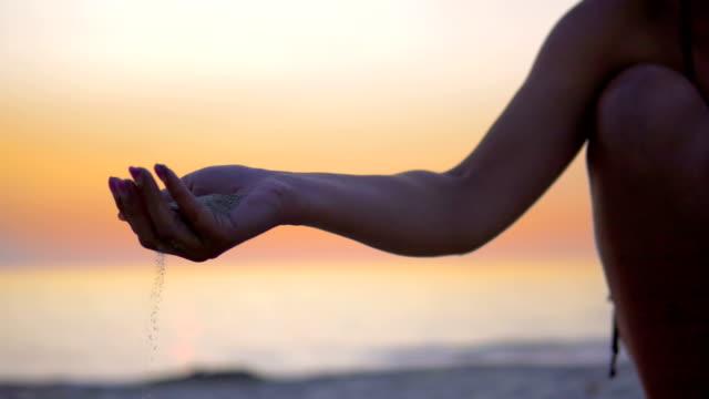strandsand strömt zwischen weiblichen modellfingern gegen denstrand sonnenuntergang - vollzeit elternteil stock-videos und b-roll-filmmaterial