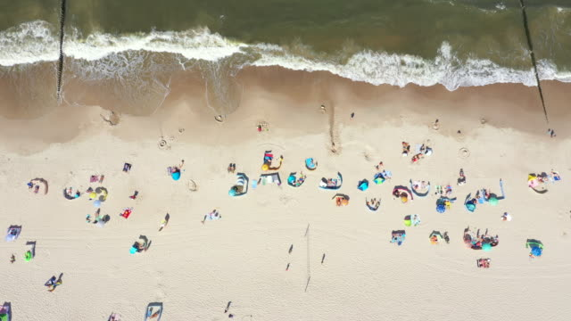 beach showing colourful umbrellas and people relaxing on a summer day. baltic sea. aerial view. hel - polska filmów i materiałów b-roll