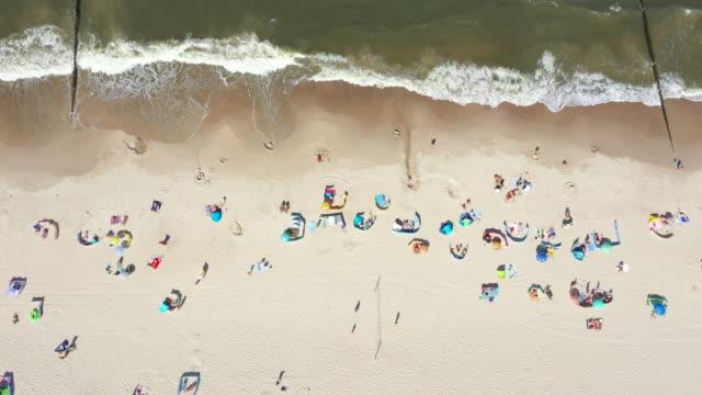 strand mit bunten sonnenschirmen und menschen, die sich an einem sommertag entspannen. ostsee. luftbild. hel - sun chair stock-videos und b-roll-filmmaterial