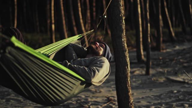 vídeos de stock e filmes b-roll de beach sunset. having fun on hammock - man admires forest