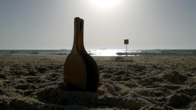 Beach tennis rackets on the background of the sea. Sunset time. video