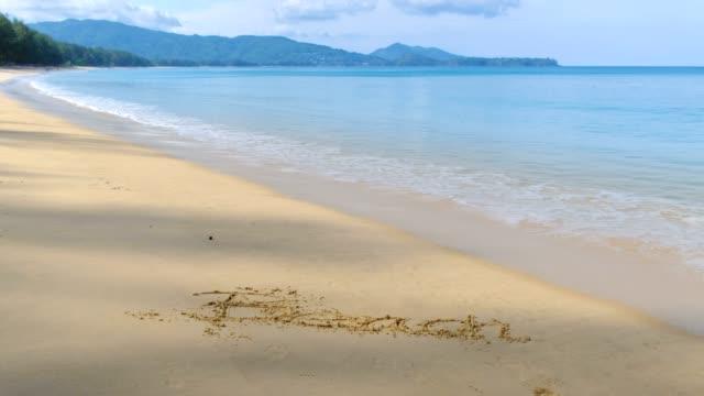 vidéos et rushes de texte de plage sur le sable et les vagues douces s'écrasant sur la plage de phuket avec des vagues mousseuses venant au rivage, l'eau bleue de mer - mer d'andaman