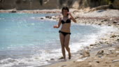 dd43da75270 Beautiful woman in the black bikini enjoying perfect sunny day walking on  the ...