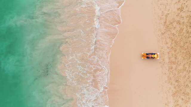 Beach vacation in paradise tropical island, sexy suntan woman relaxing on idyllic summer background in clear water and beach. Top view aerial drone video