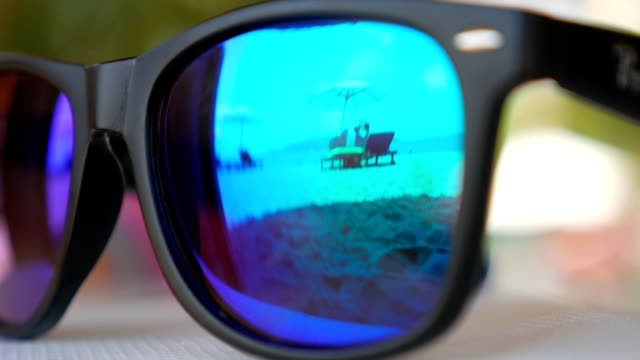 Beach with loungers and parasol reflected in blue mirrored sunglasses