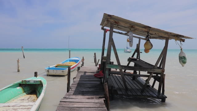 Beach with pier shack and boats on Caribbean Island - Belize / Caye Caulker